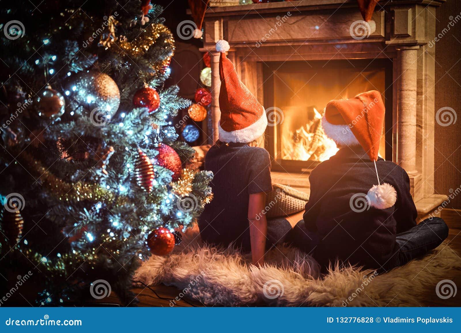 后面戴圣诞老人的帽子的看法、兄弟和姐妹温暖在一个壁炉旁边在为圣诞节装饰的客厅