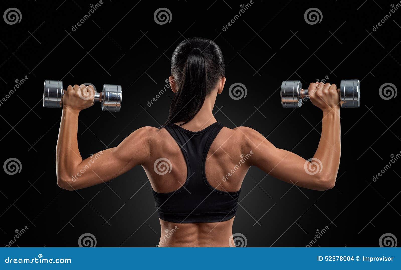 后面的训练肌肉的健身妇女有哑铃的