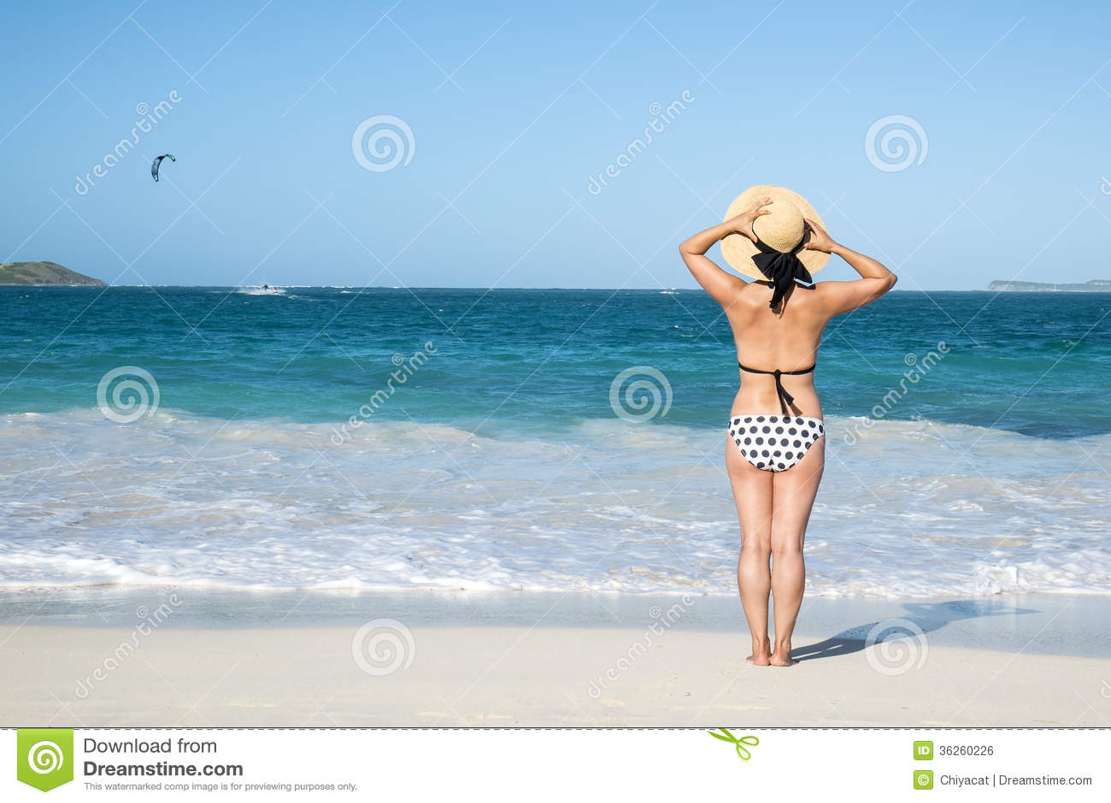 后面观点的站立在海滩1的圆点比基尼泳装的一名妇女