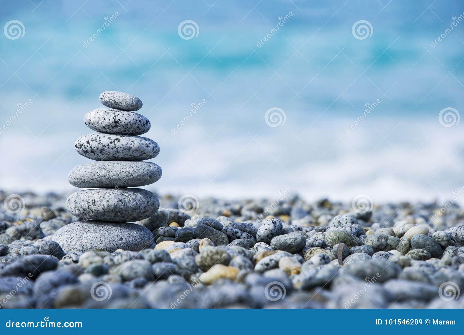 向在象征温泉概念有迷离海背景的Pebble海滩的金字塔扔石头