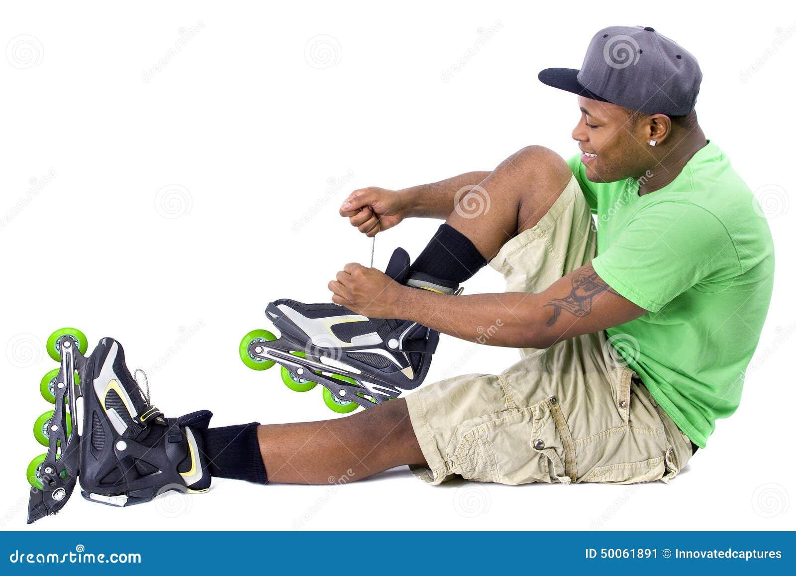黑人h动漫_摆在与直排轮式溜冰鞋的年轻成人黑人滑冰.