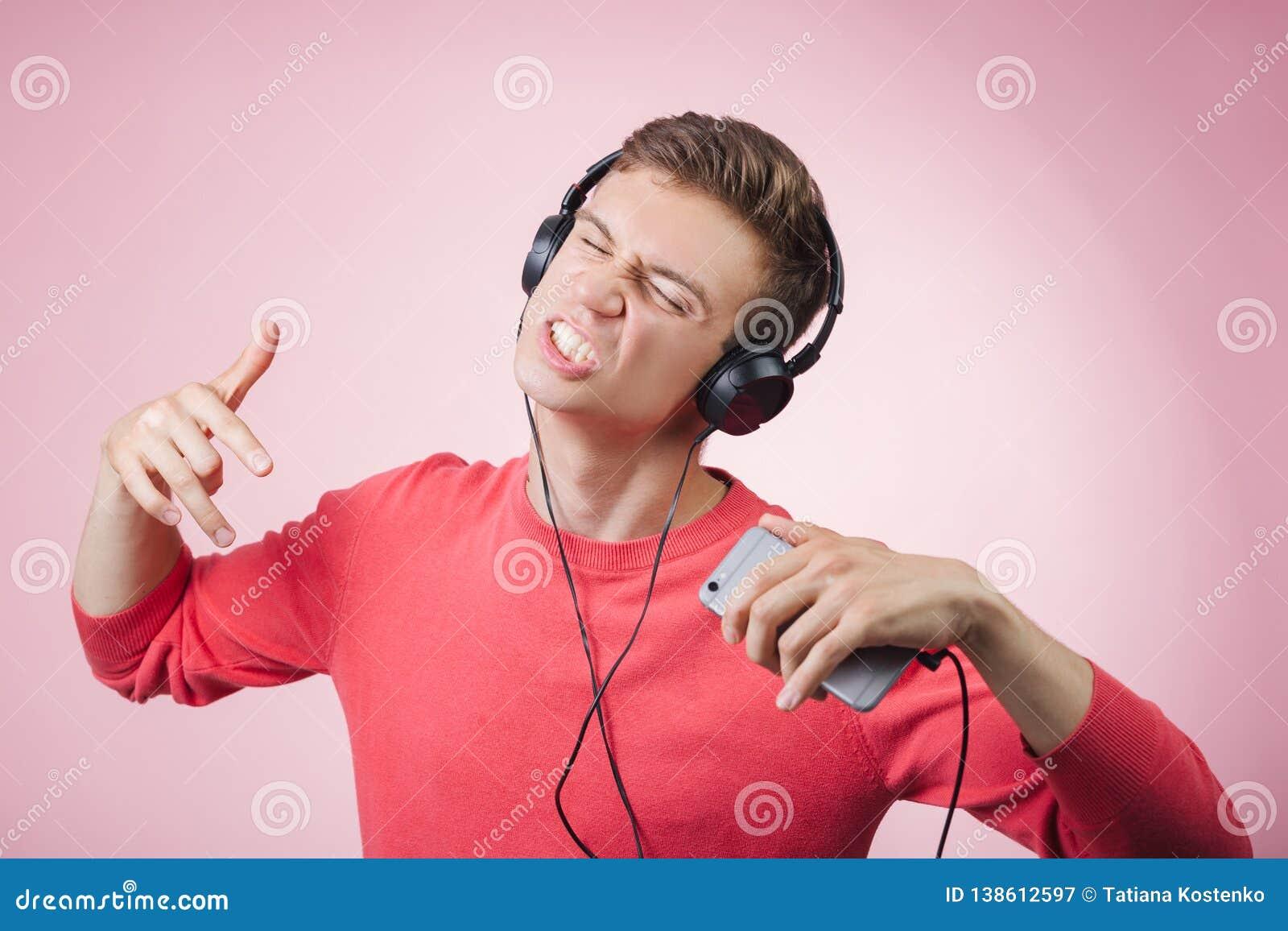 听一年轻的帅哥的画象有耳机的微笑和与智能手机的音乐