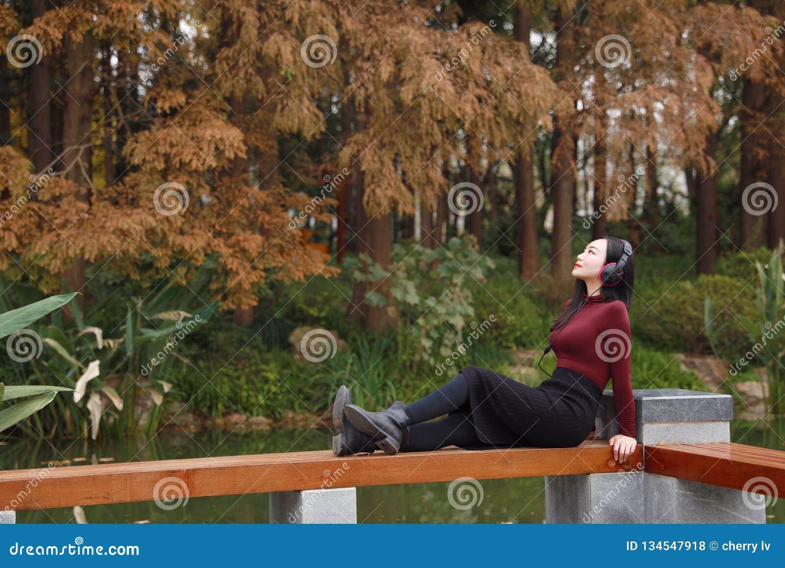 听到与耳机的音乐的年轻亚裔中国妇女坐在树下