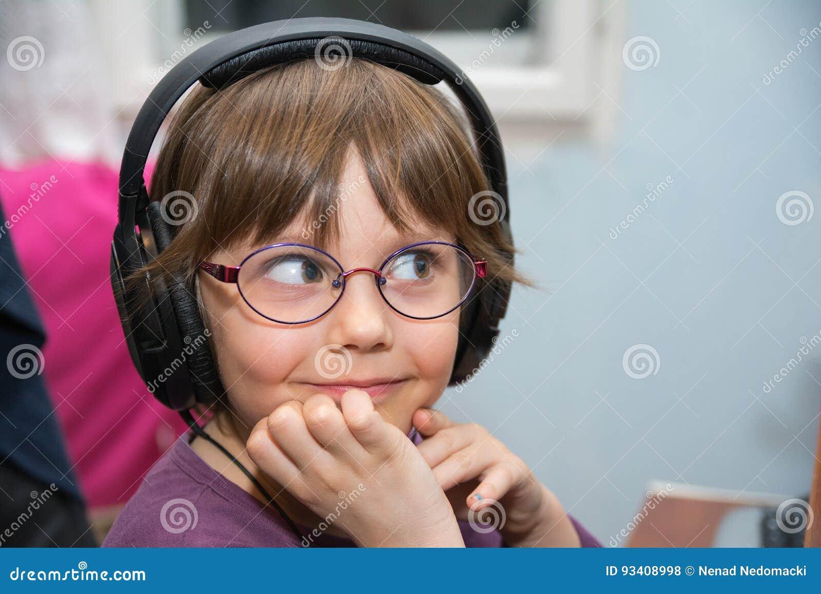听到与耳机的音乐的美丽的女孩