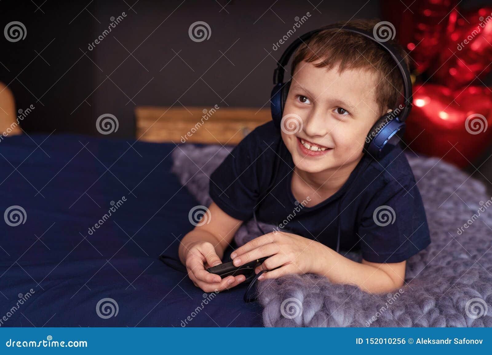 听到在在床上的耳机的音乐的男孩
