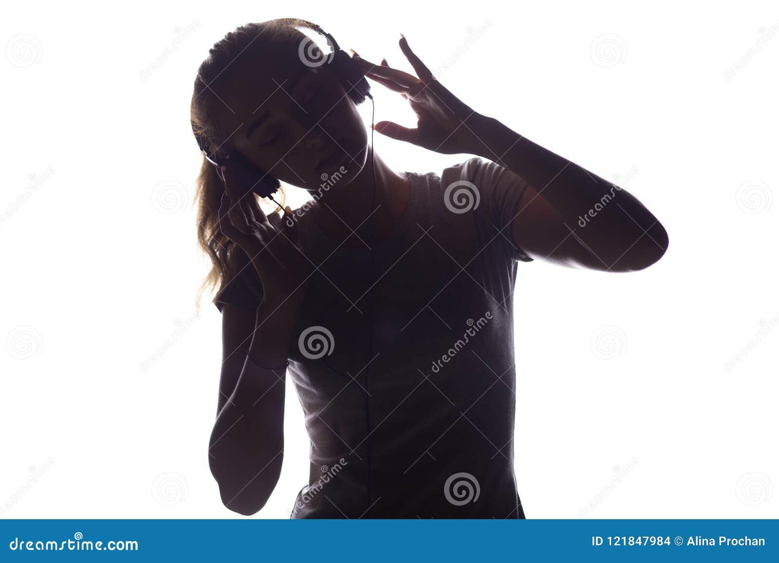 听到在耳机的音乐的妇女剪影
