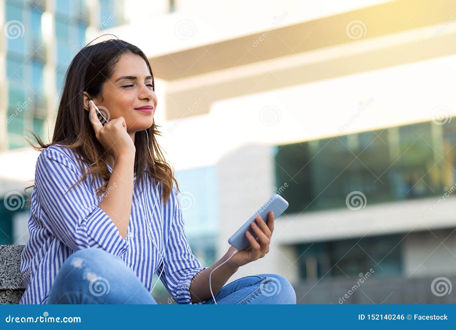 听到在耳机的音乐的微笑的妇女,享受晴朗的天气户外