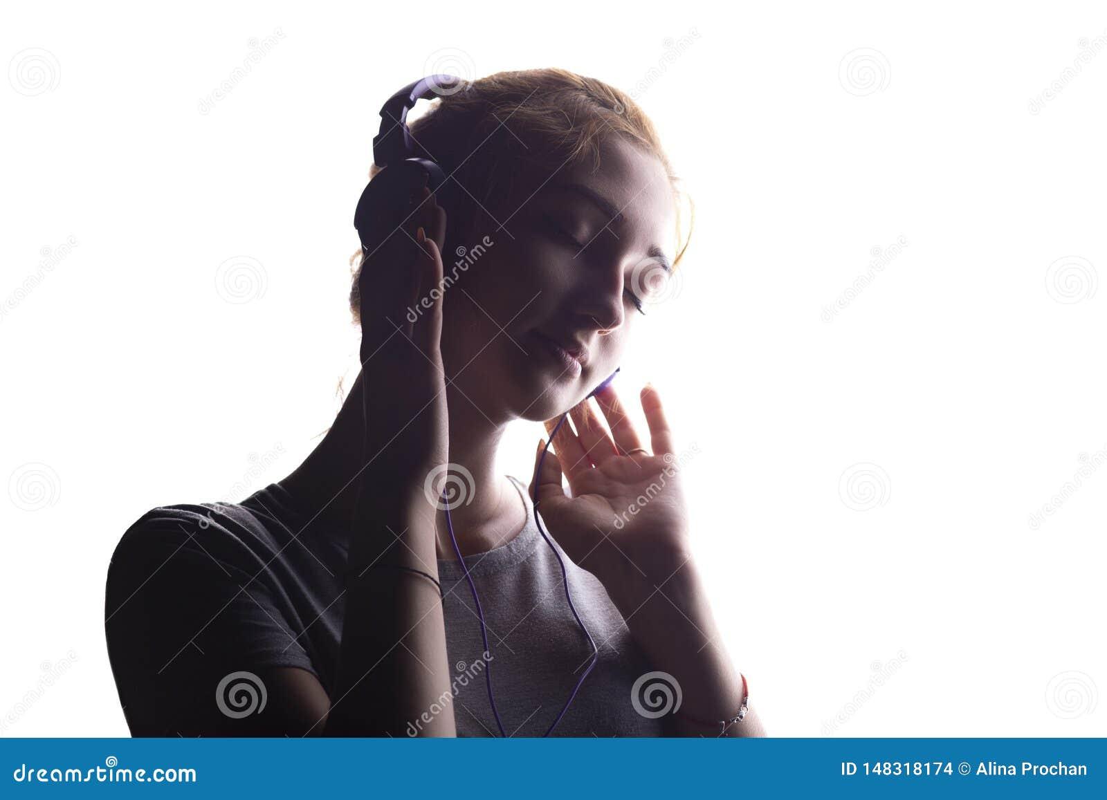 听到在耳机的音乐,年轻女人放松在白色被隔绝的背景,概念的一个浪漫女孩的剪影