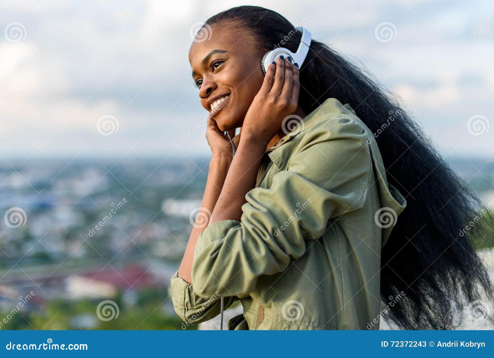 听到音乐的华美的年轻黑人非裔美国人的妇女特写镜头画象  在背景的被弄脏的都市风景