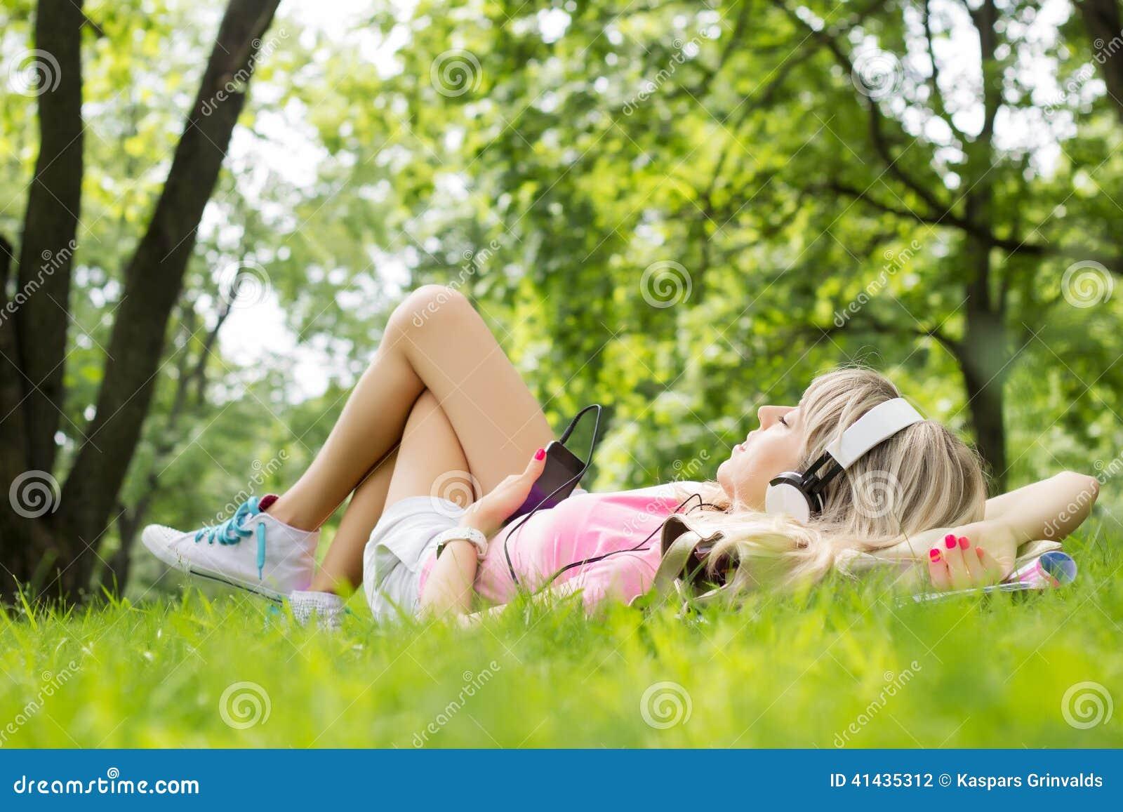 听到音乐的少妇,当放下在草时