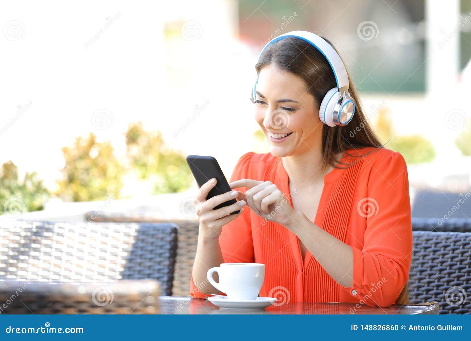 听到音乐的愉快的妇女在咖啡馆