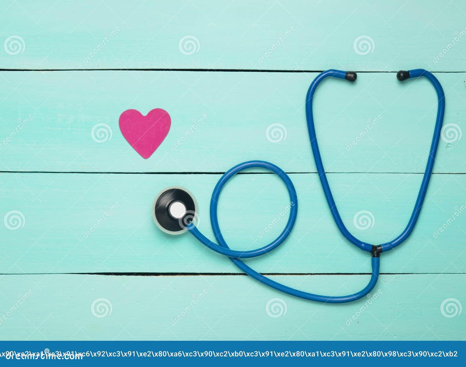 听诊器和心脏在一张蓝色木桌上 诊断的心血管病心脏病学设备 顶视图 平的位置