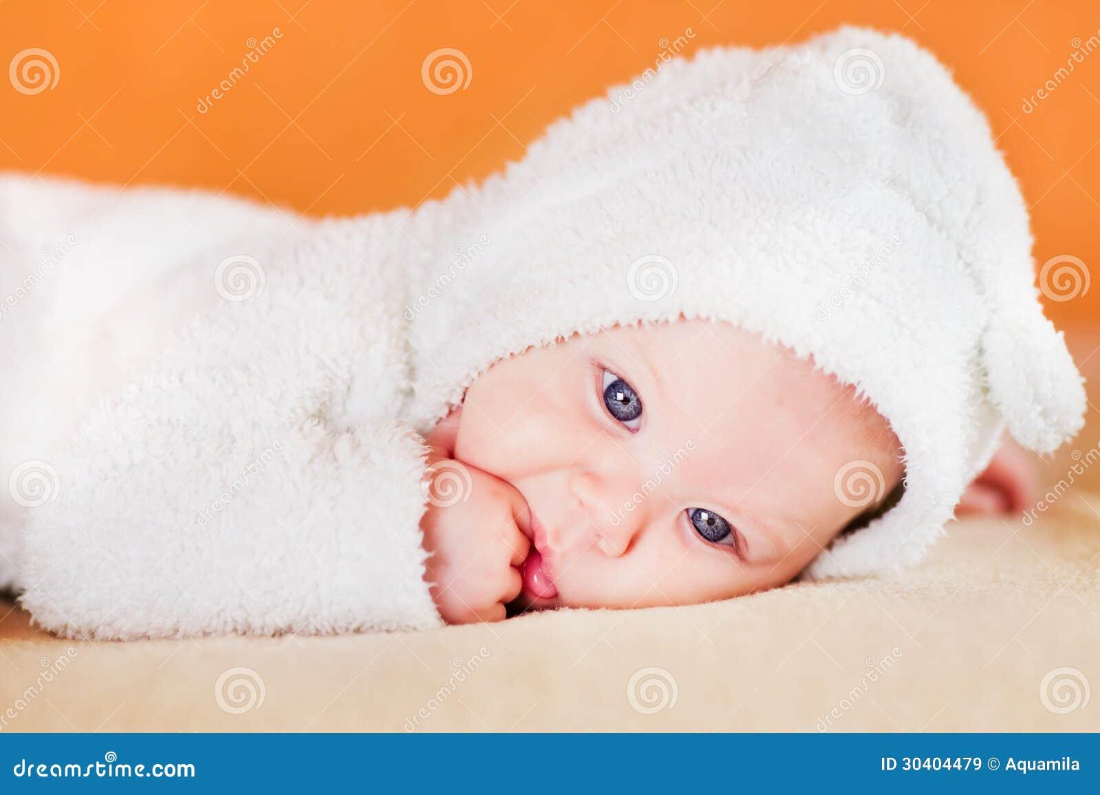 吮他的手指的逗人喜爱的矮小的婴孩