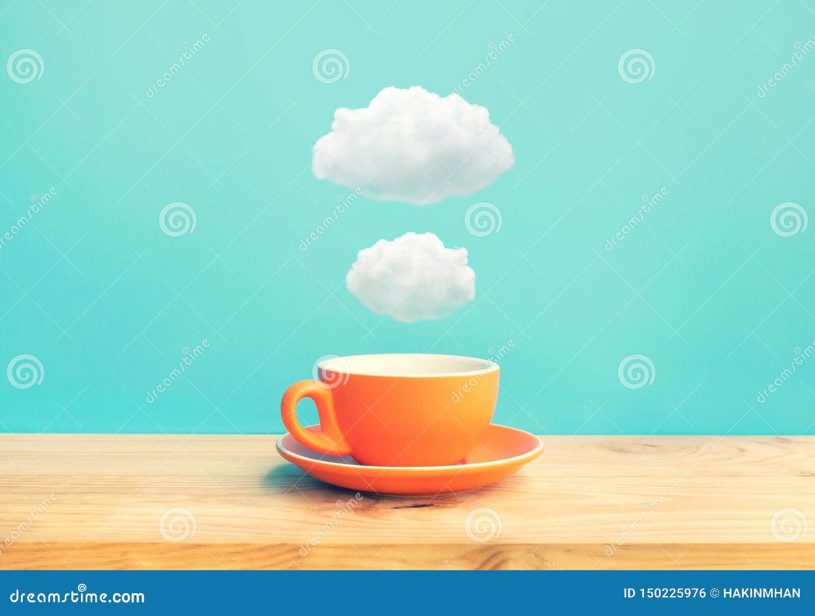 启发与一杯咖啡的创造性概念在木酒吧桌上的与在天空蔚蓝颜色背景的一些云彩