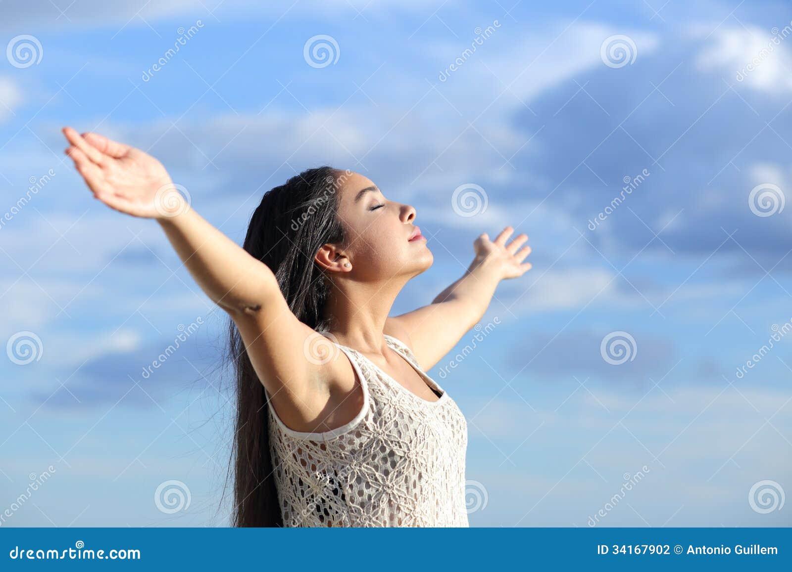 呼吸与被举的胳膊的美丽的阿拉伯妇女新鲜空气