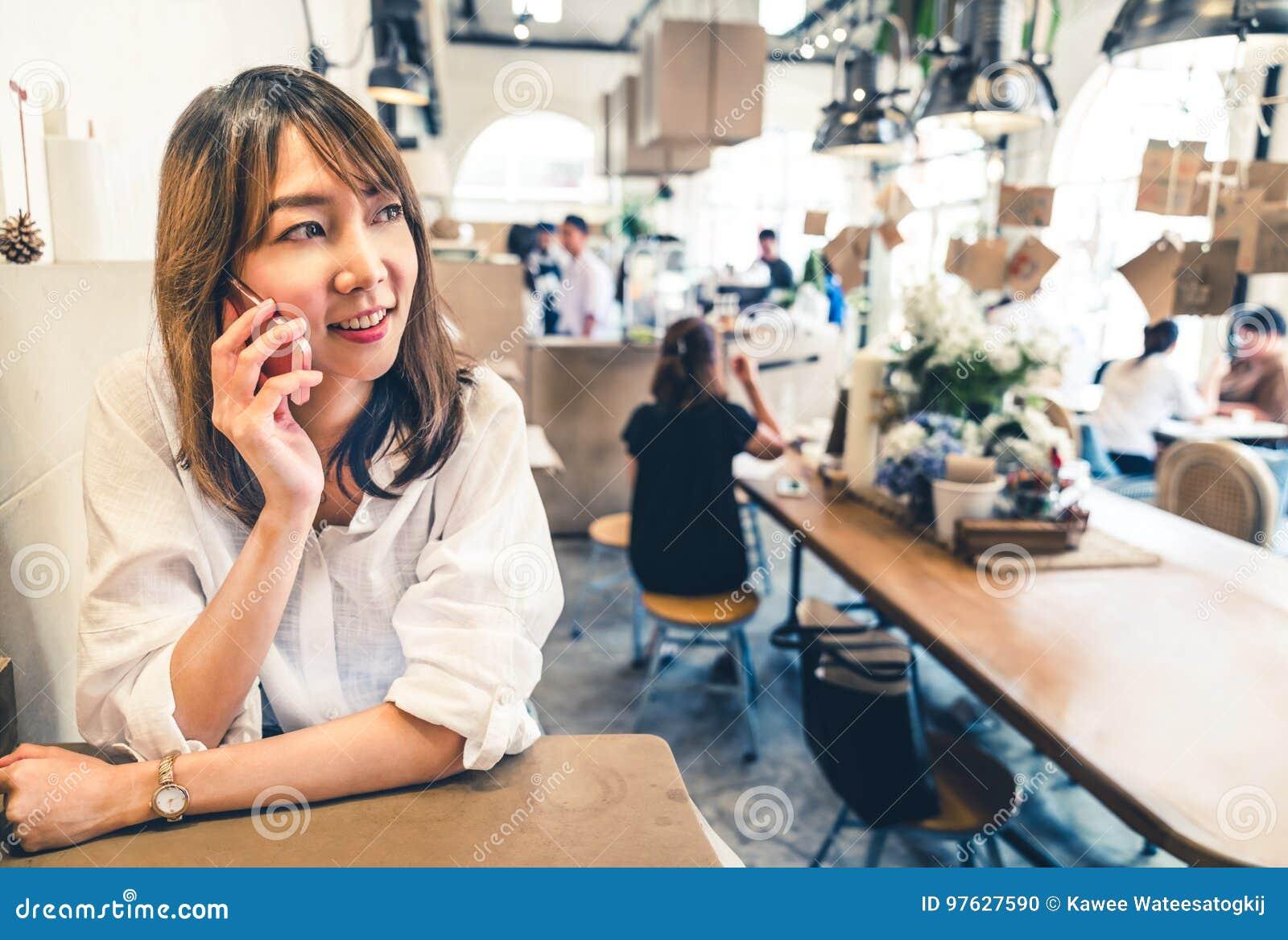 年轻和美丽的亚裔妇女谈话在手机在咖啡店、通信或者咖啡馆偶然生活方式概念
