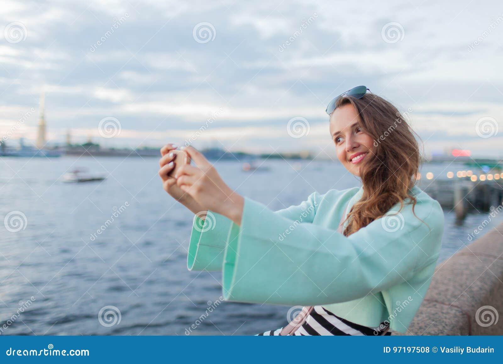 年轻和美丽的女孩坐河的堤防 她看日落和采取在您的电话的一selfie 圣徒