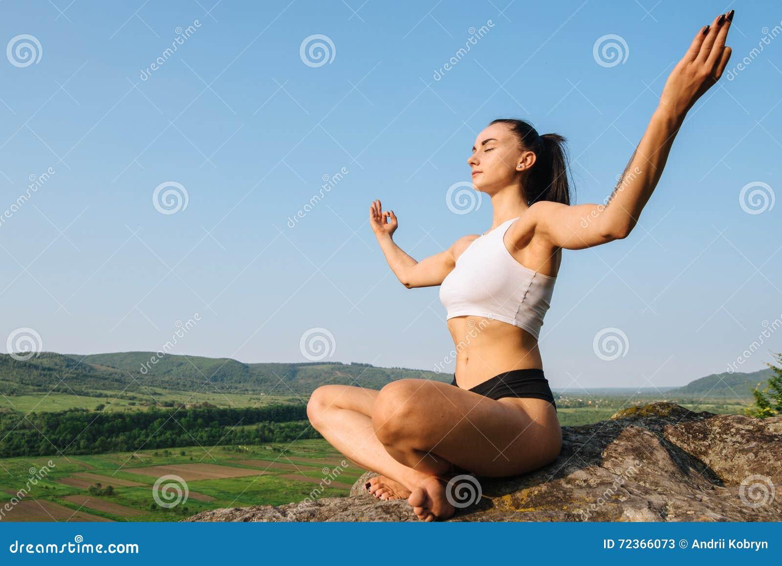 和谐的片刻 美丽的坚强的深色的在岩石和放松的女子实践的瑜伽