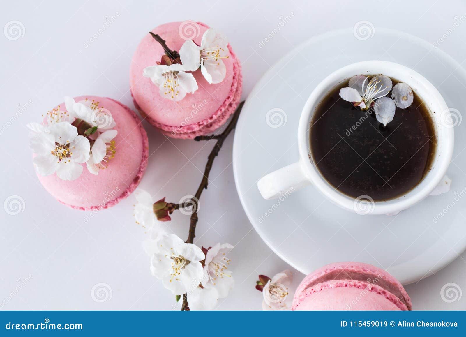 咖啡与桃红色macarons和白花的