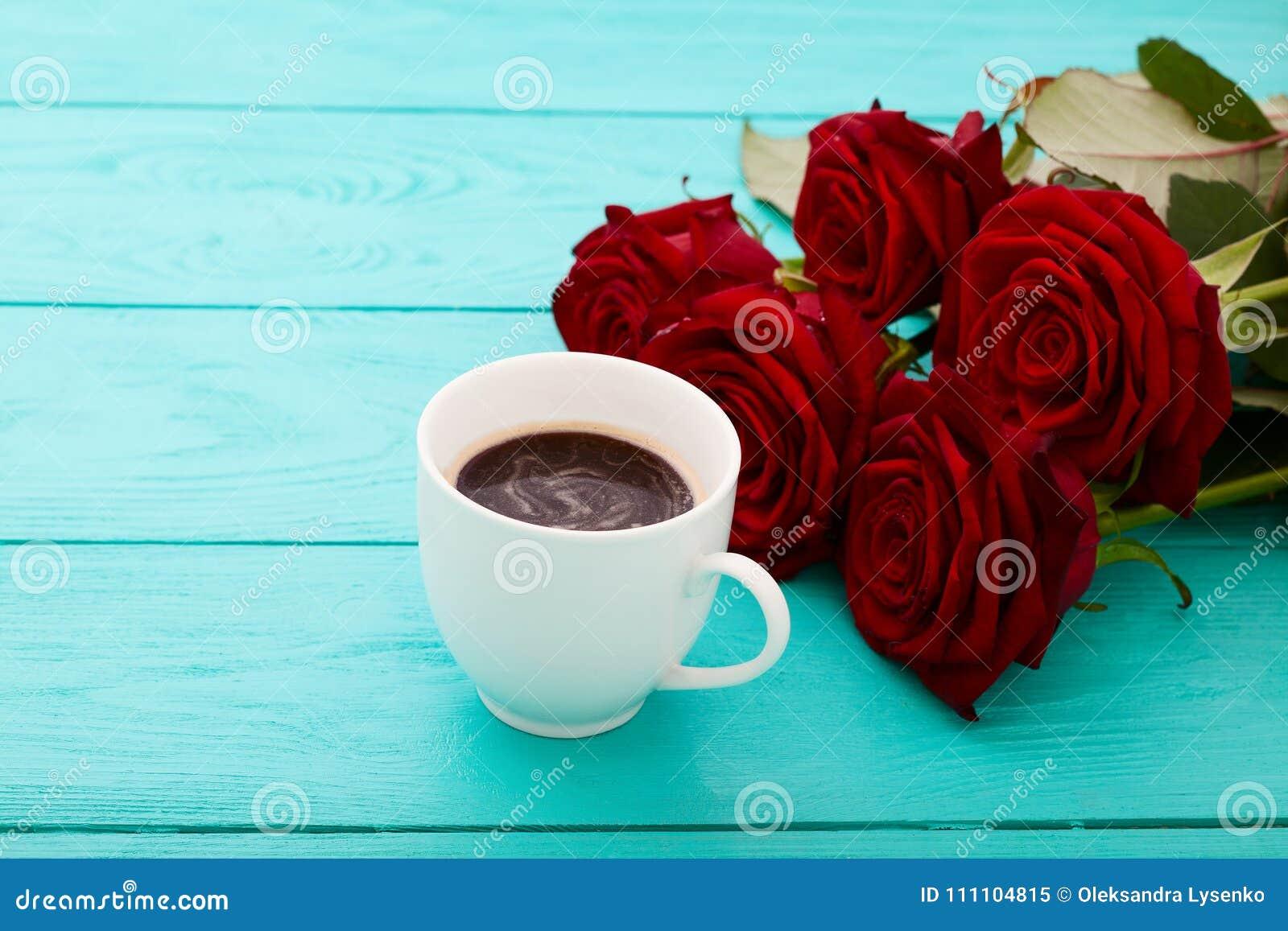 咖啡在蓝色木桌上的 顶视图 嘲笑 热的饮料 选择聚焦 红色唤醒花束 华伦泰母亲节