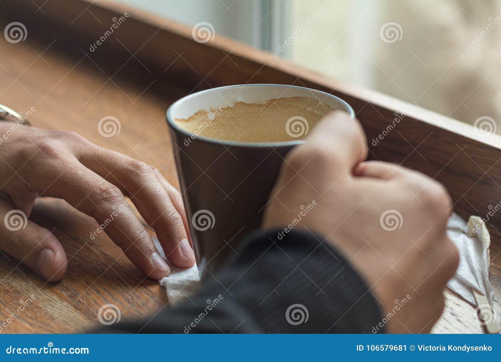 咖啡在说谎在咖啡馆的一张桌上的一个人的手上