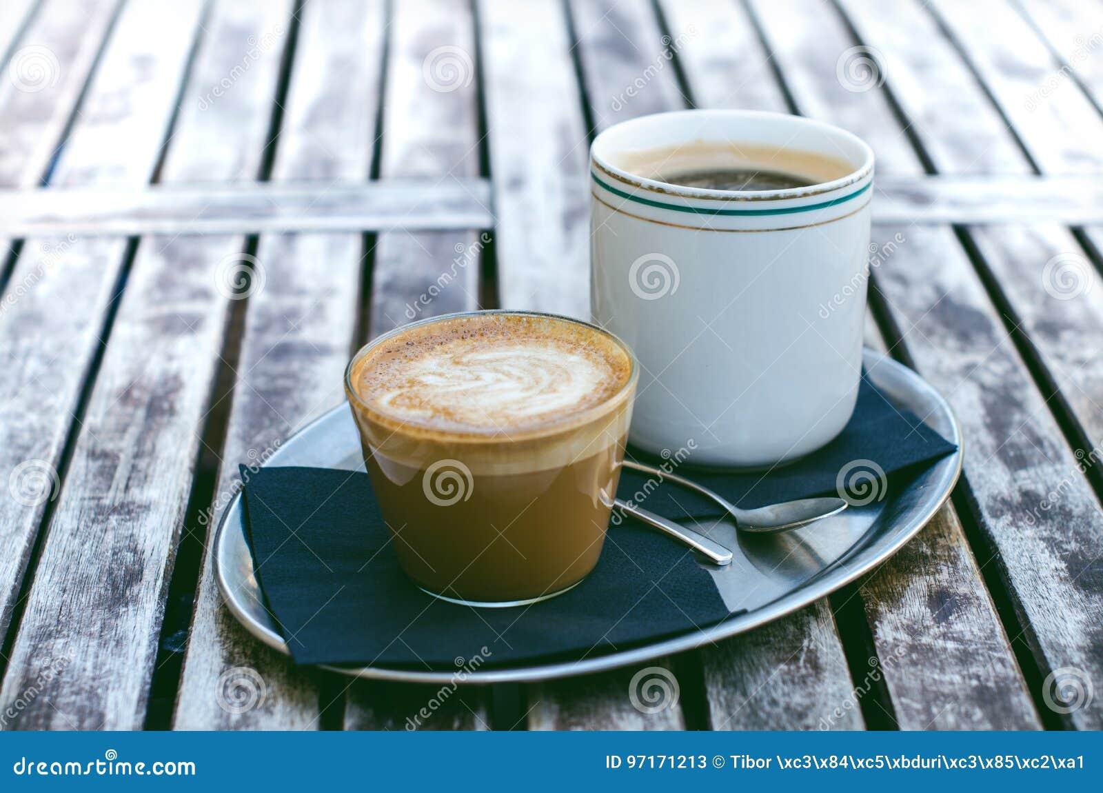 咖啡杯和蛋糕在一张木葡萄酒桌上 行家概念 妇女饮料咖啡 杯americano和macchiato