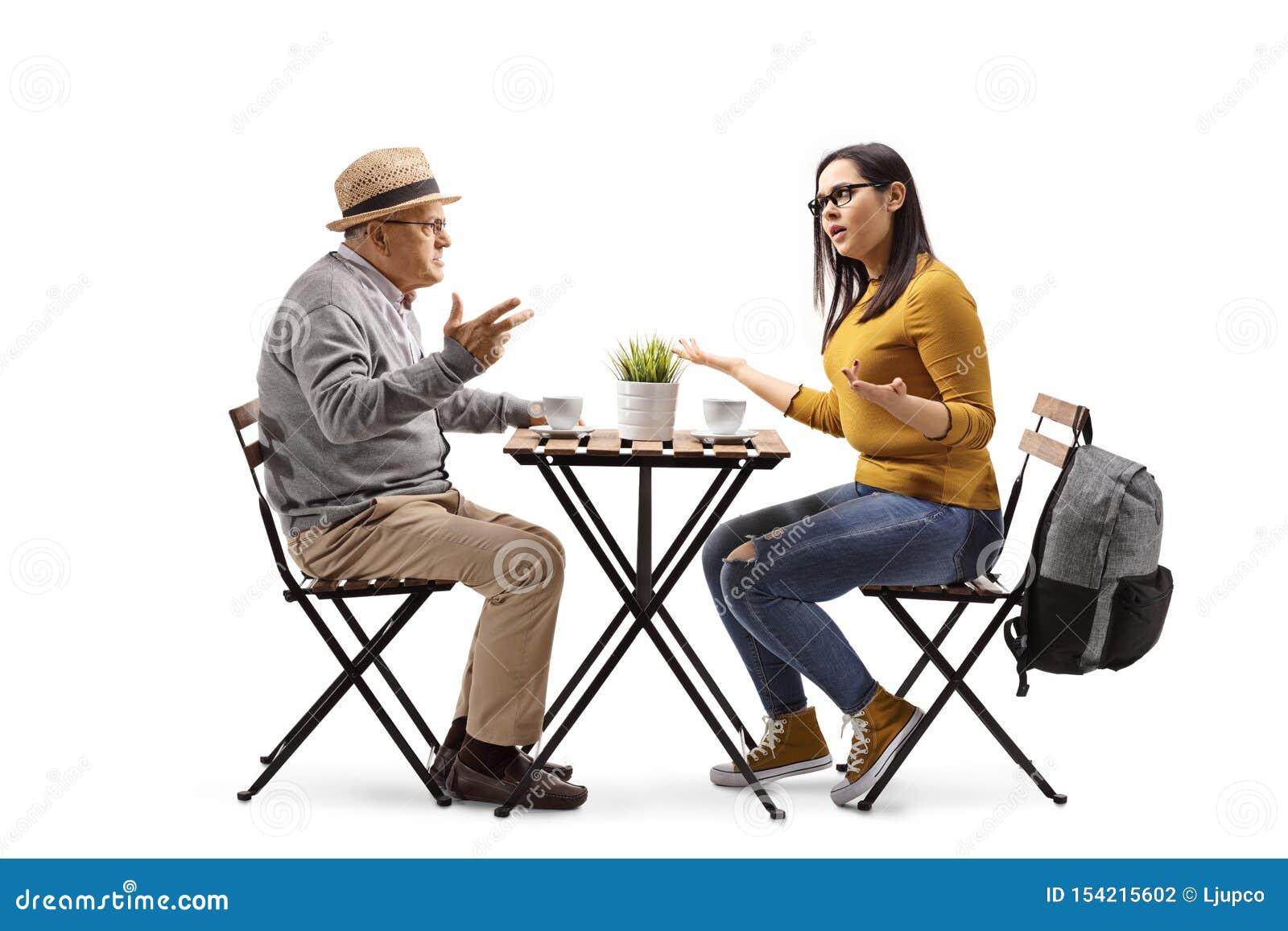 咖啡馆的恼怒的女生坐在桌上和争论与一个年长人