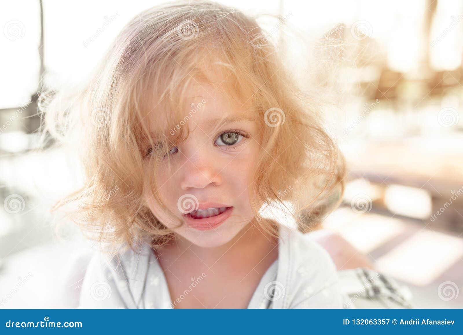 哀伤地看在被弄脏的晴朗的照相机的相当年轻矮小的白肤金发的苍白不快乐的喜怒无常的没有朋友的儿童女孩特写镜头画象