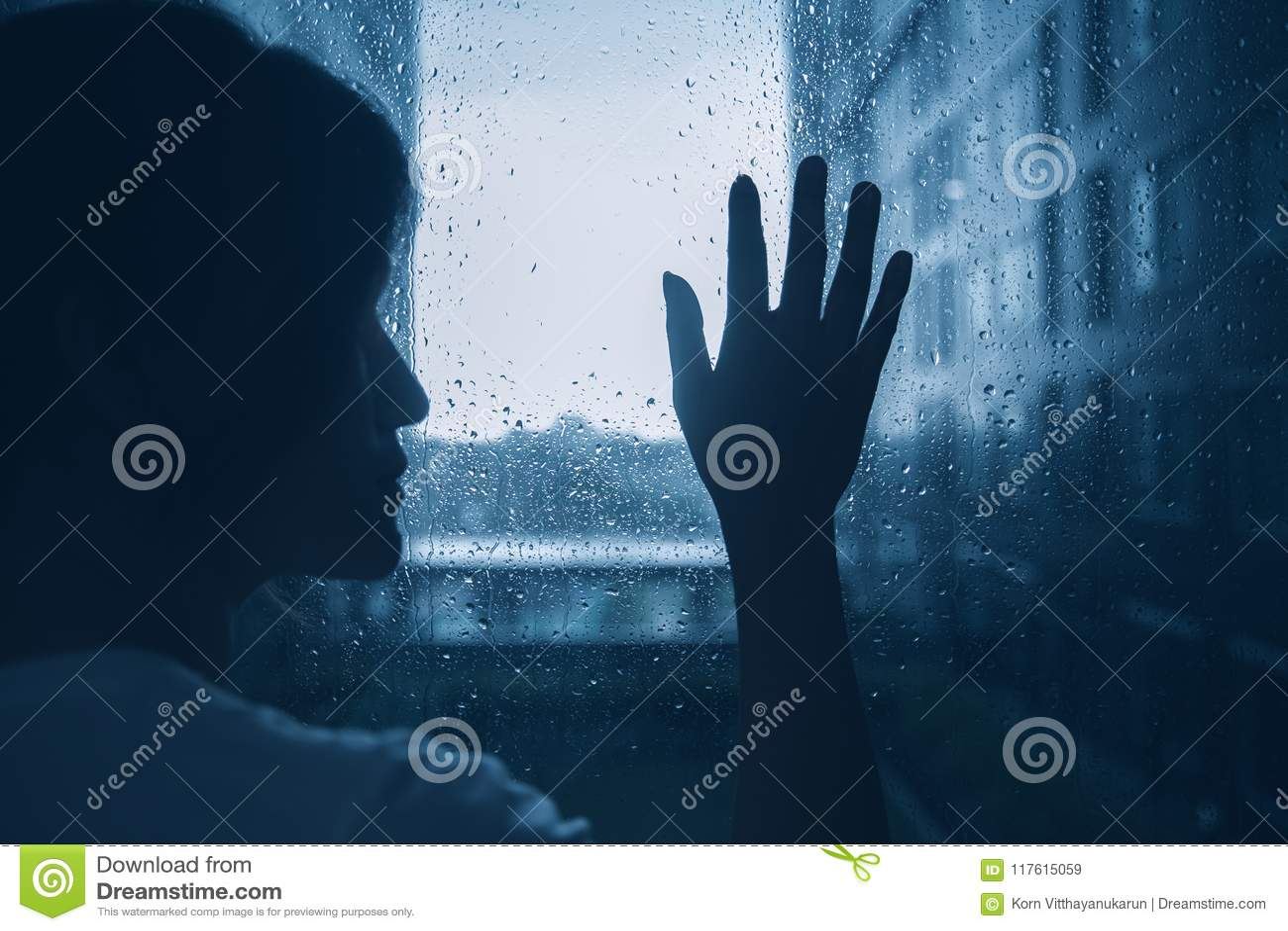 哀伤的偏僻的消沉心情妇女剪影接触玻璃窗雨天
