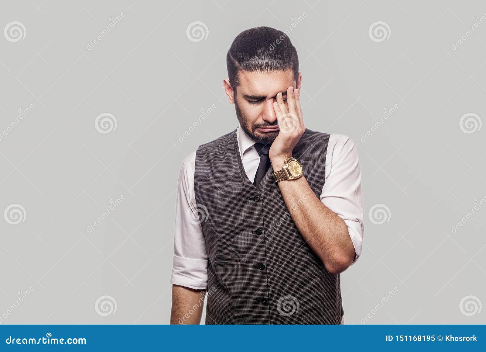 哀伤的单独沮丧的英俊的有胡子的深色的人画象白色衬衫和背心身分的,使头保持向下,接触