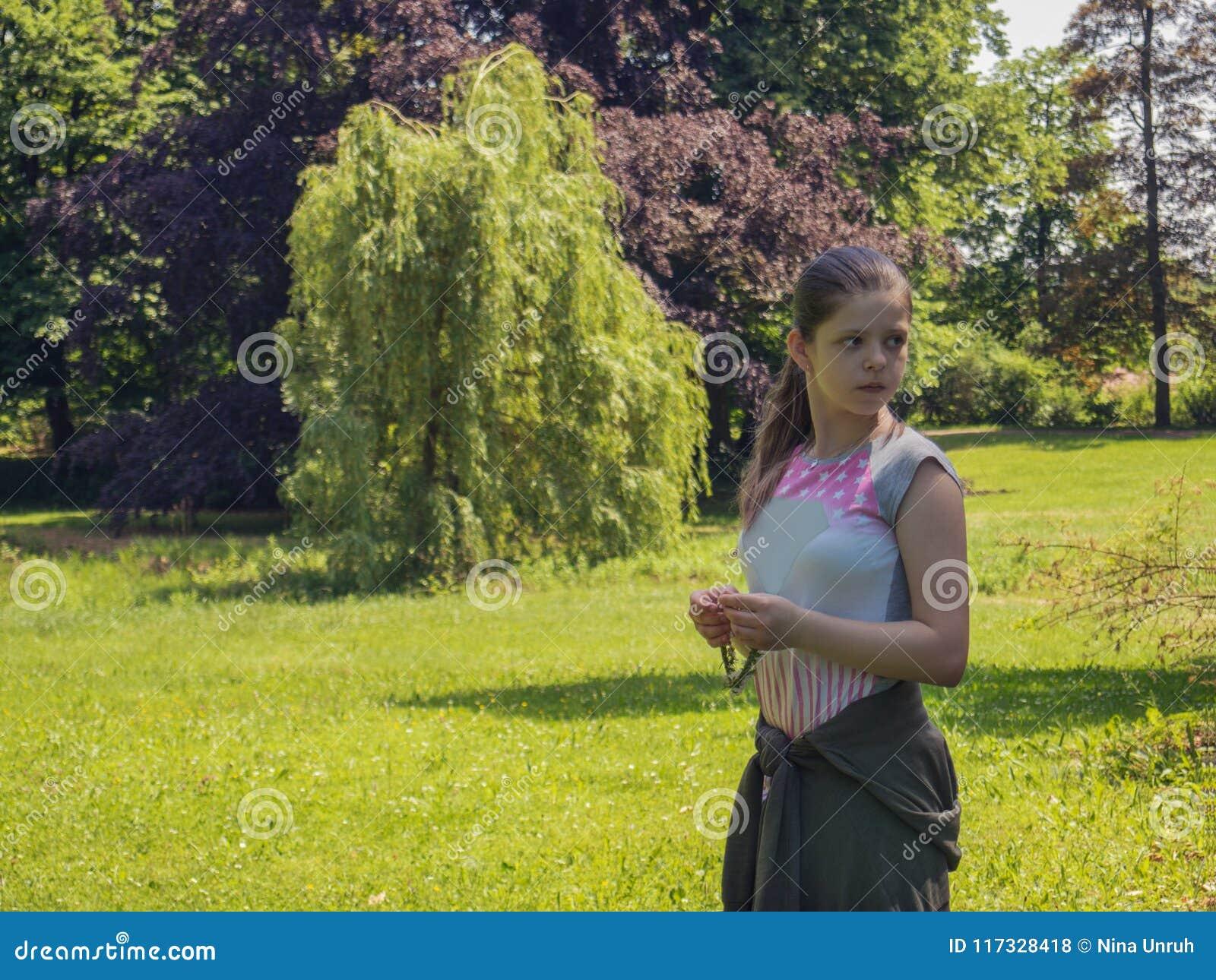 哀伤的孤独的白种人十几岁的女孩在背景的树包围的公园