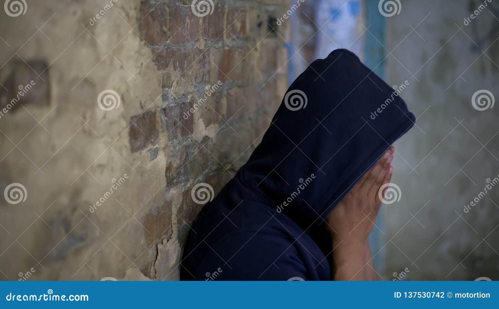 哀伤的少年哭泣在被放弃的房子里的,生活毁坏被战争,哀痛和哀情