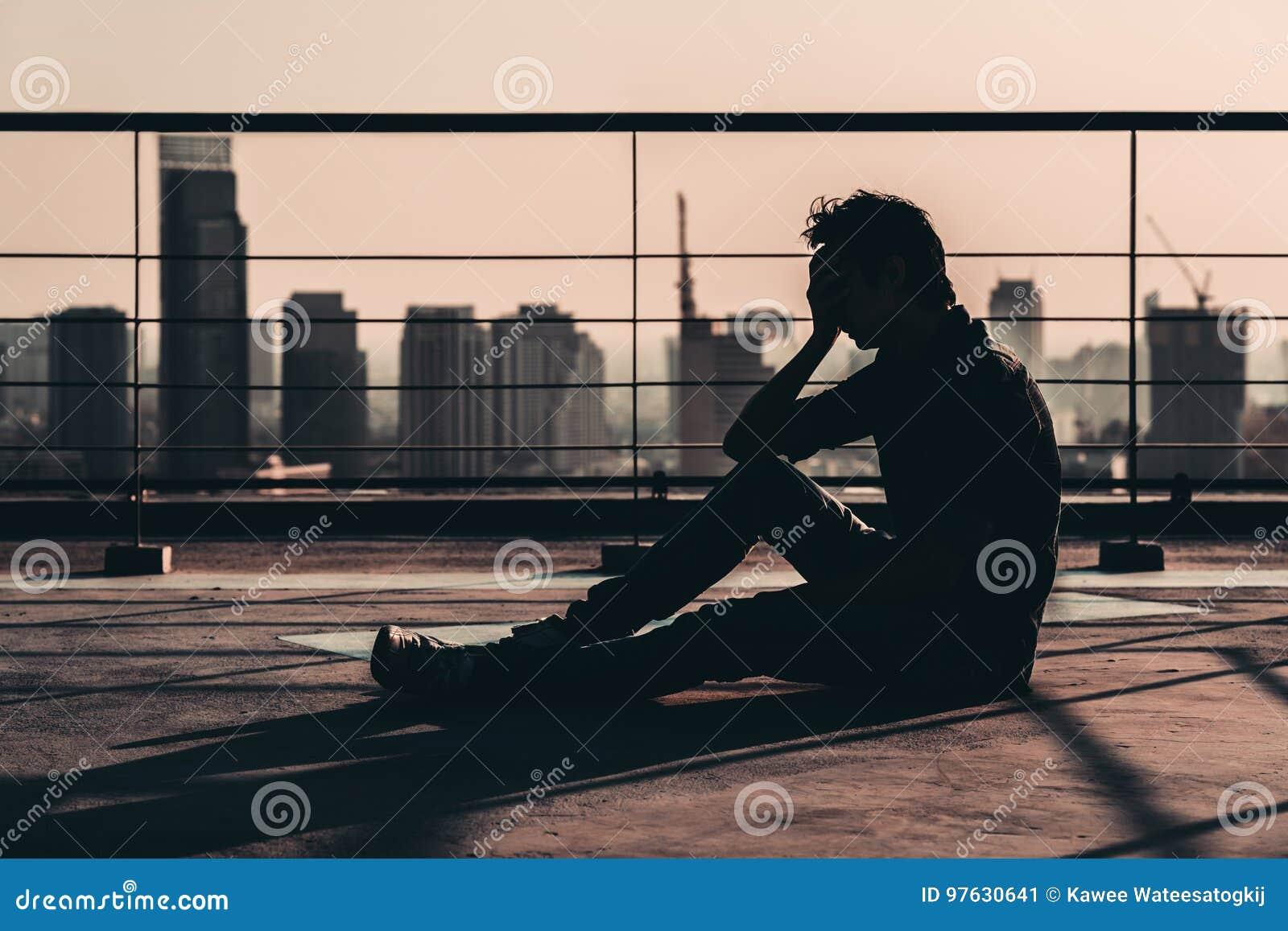 哀伤的沮丧的亚裔人丧失的希望和啼声剪影,坐大厦屋顶在日落,黑暗的心情口气