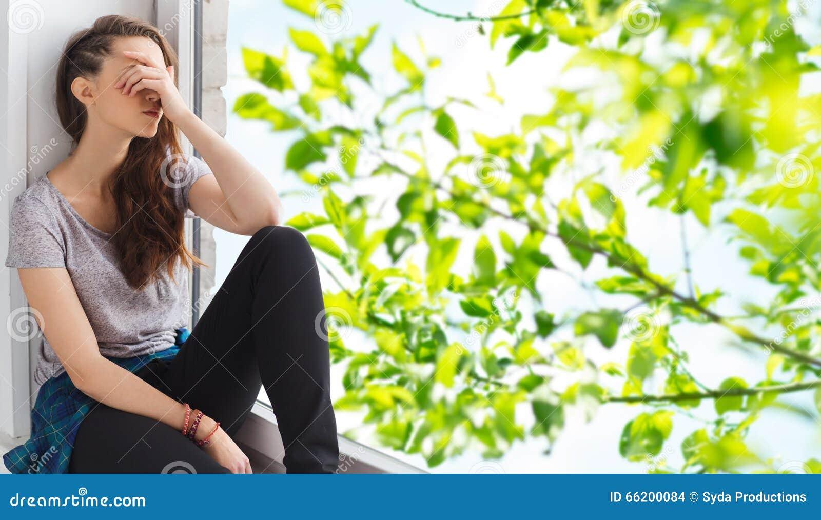 几岁_哀伤的相当十几岁的女孩坐窗台