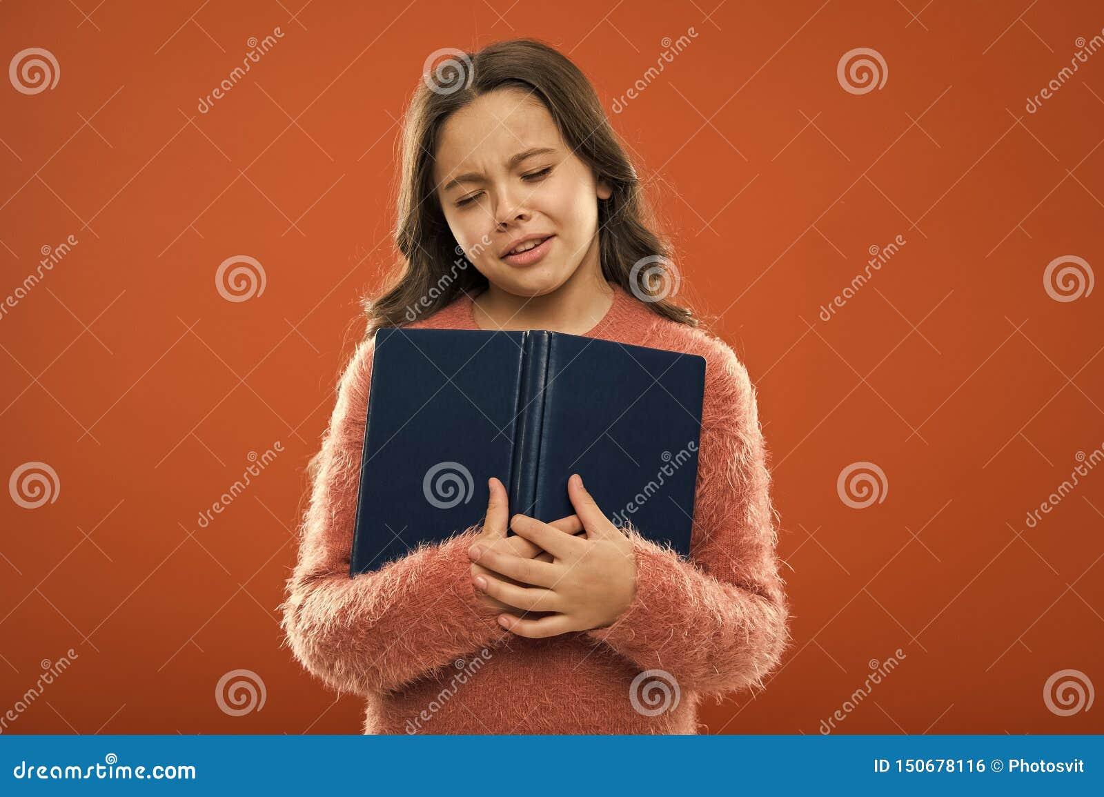 哀伤的结束的故事 女孩举行书读了在橙色背景的故事 孩子享用看书 书店概念