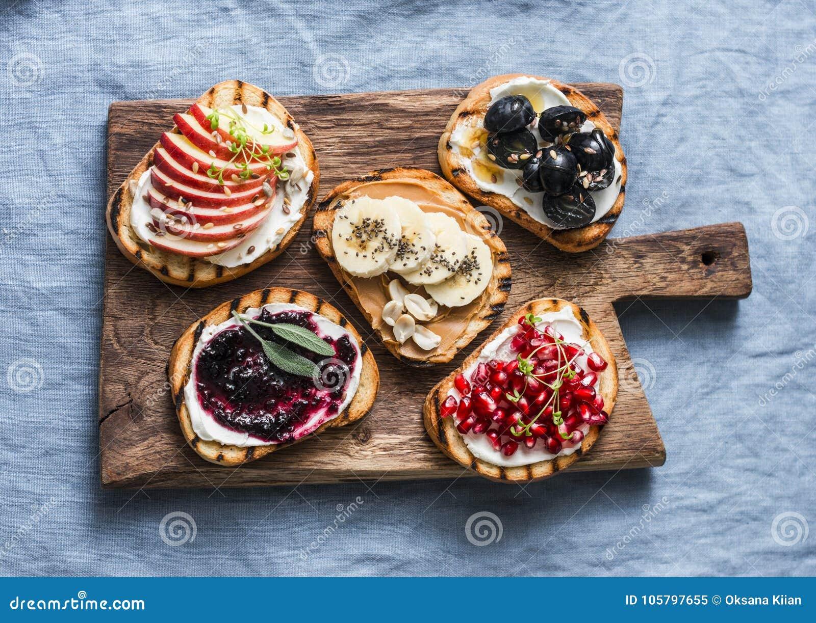 品种烤面包点心小板材三明治用乳脂干酪和苹果,石榴,果酱,葡萄,花生酱,香蕉