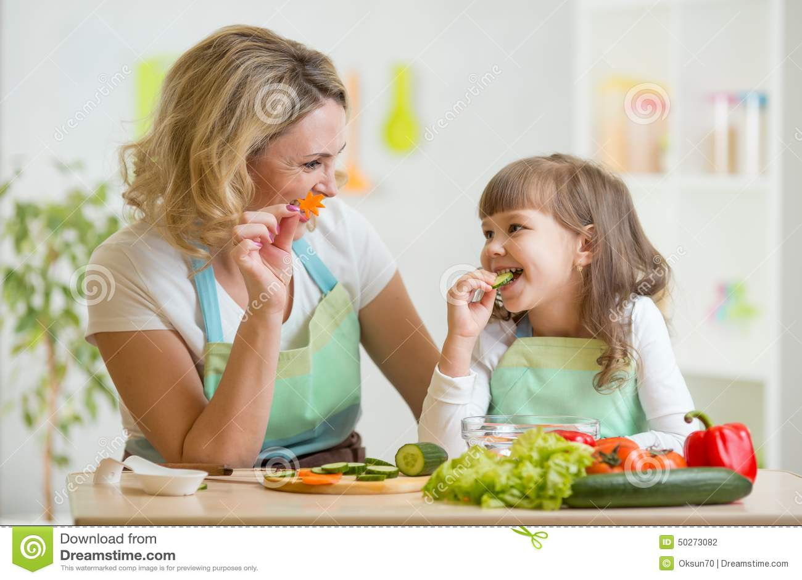 哄骗吃健康食物菜的女孩和母亲