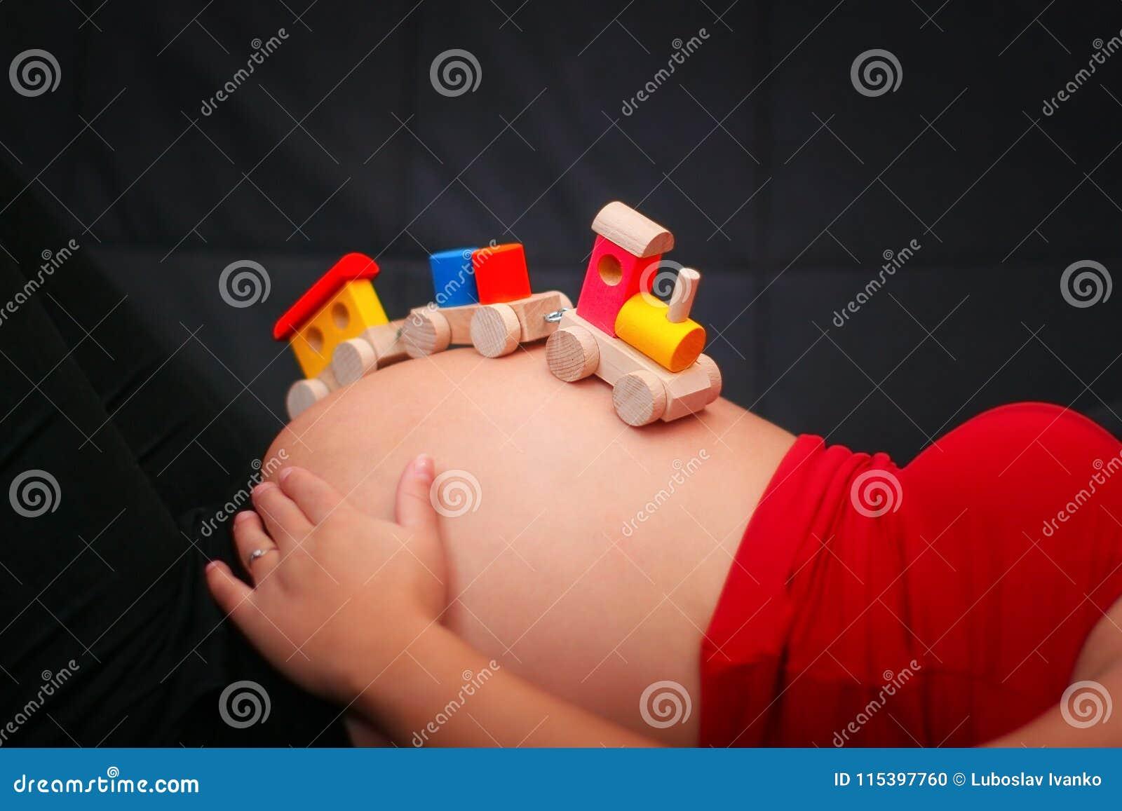 哄骗在怀孕的腹部的木火车玩具 浓缩婴孩的期望