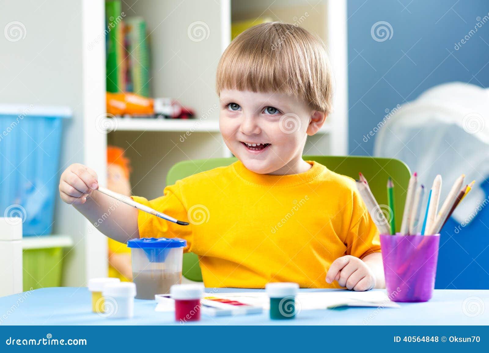 哄骗男孩绘画在桌上在儿童居室