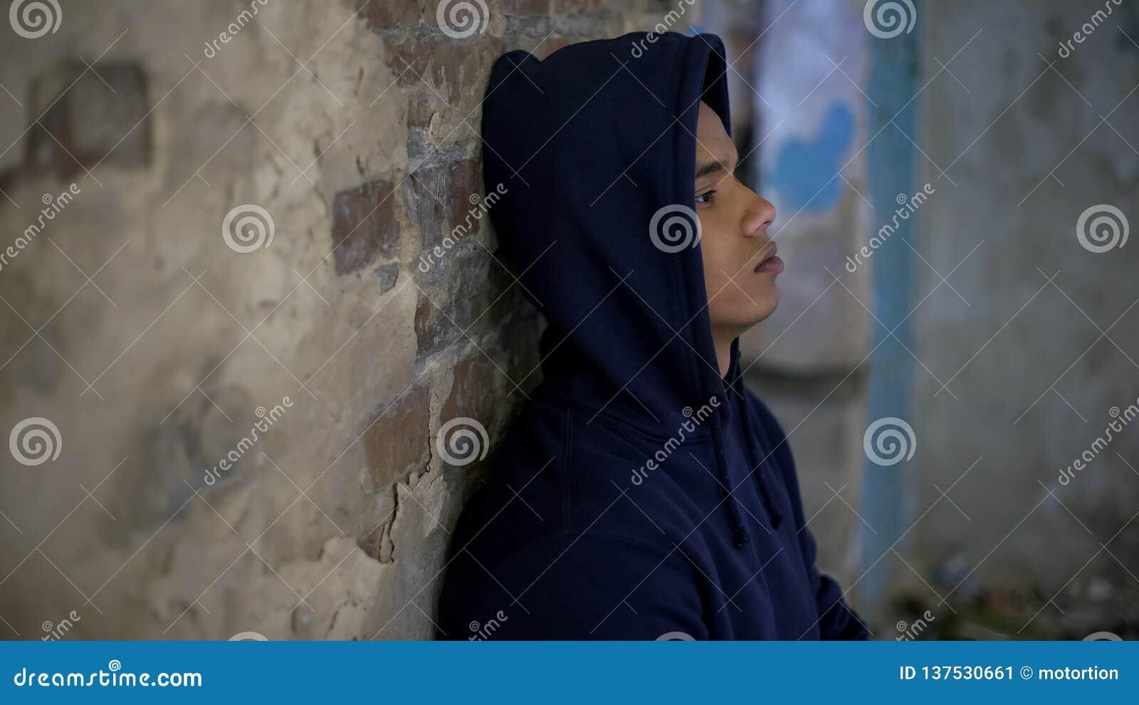 哭泣在房子里的绝望的十几岁的男孩毁坏被战争,消沉,贫穷