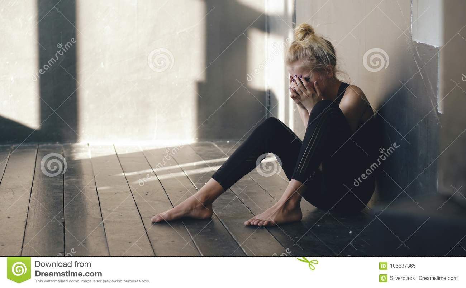 哭泣在损失perfomance以后的年轻十几岁的女孩舞蹈家特写镜头坐地板在大厅里户内