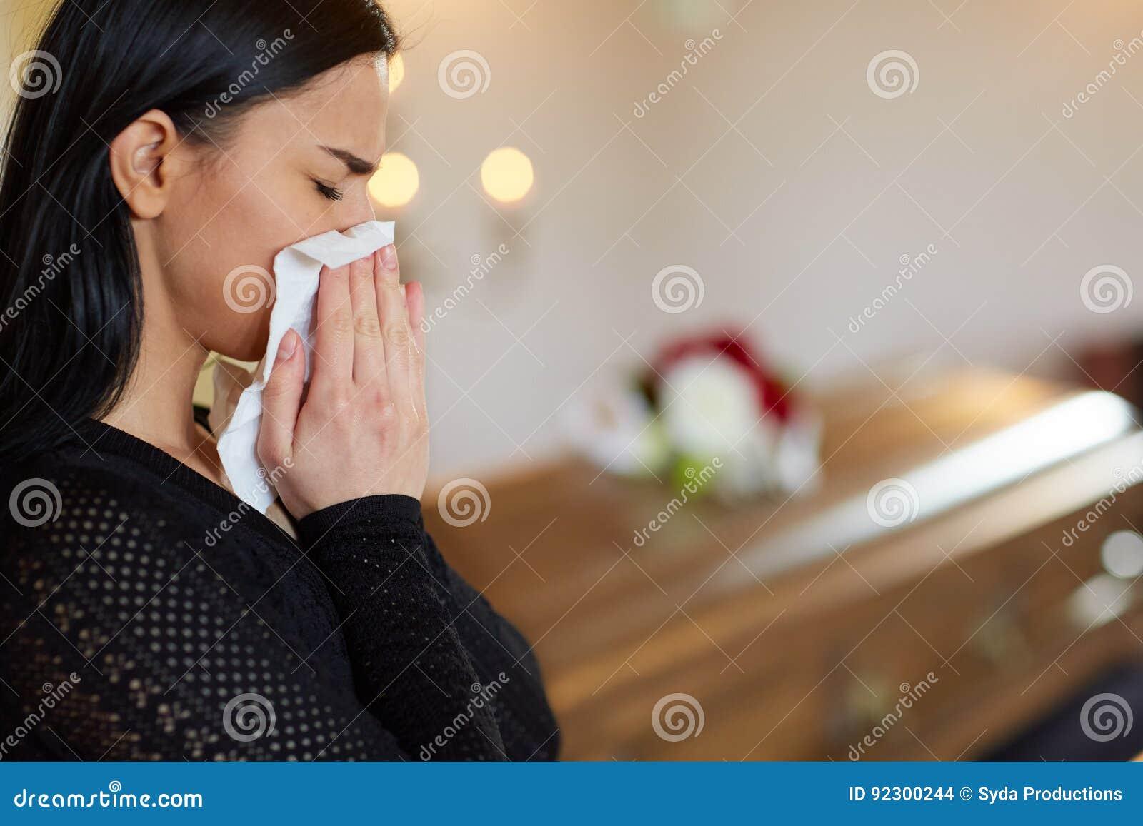 哭泣在棺材附近的妇女在葬礼在教会里
