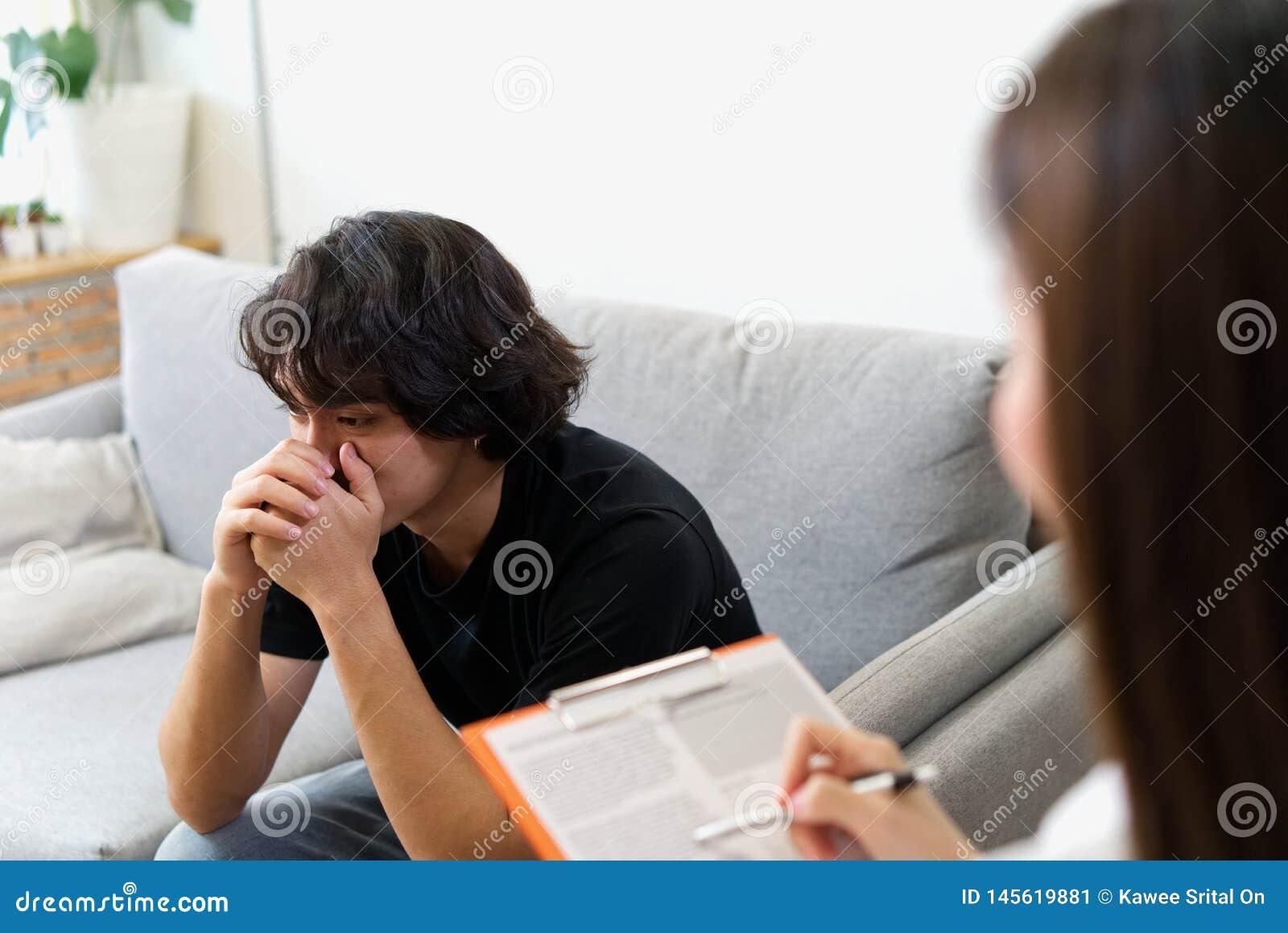 哭泣在沙发的年轻男性患者与女性心理学家协商