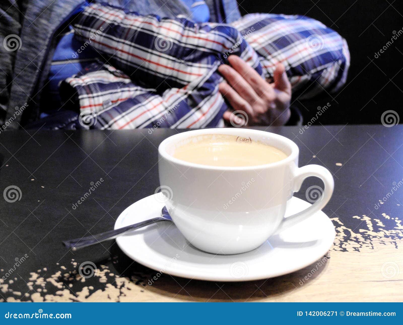 哺乳在与站立在她前面的桌上的一杯咖啡的咖啡馆的妇女 饮用的咖啡一会儿的概念