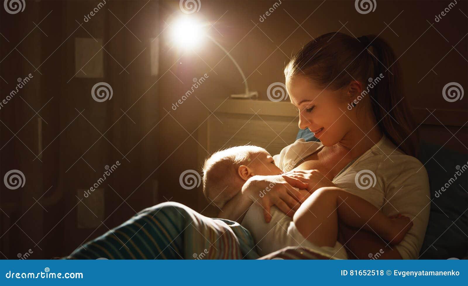 哺乳 在床黑暗夜照顾哺养的婴孩乳房