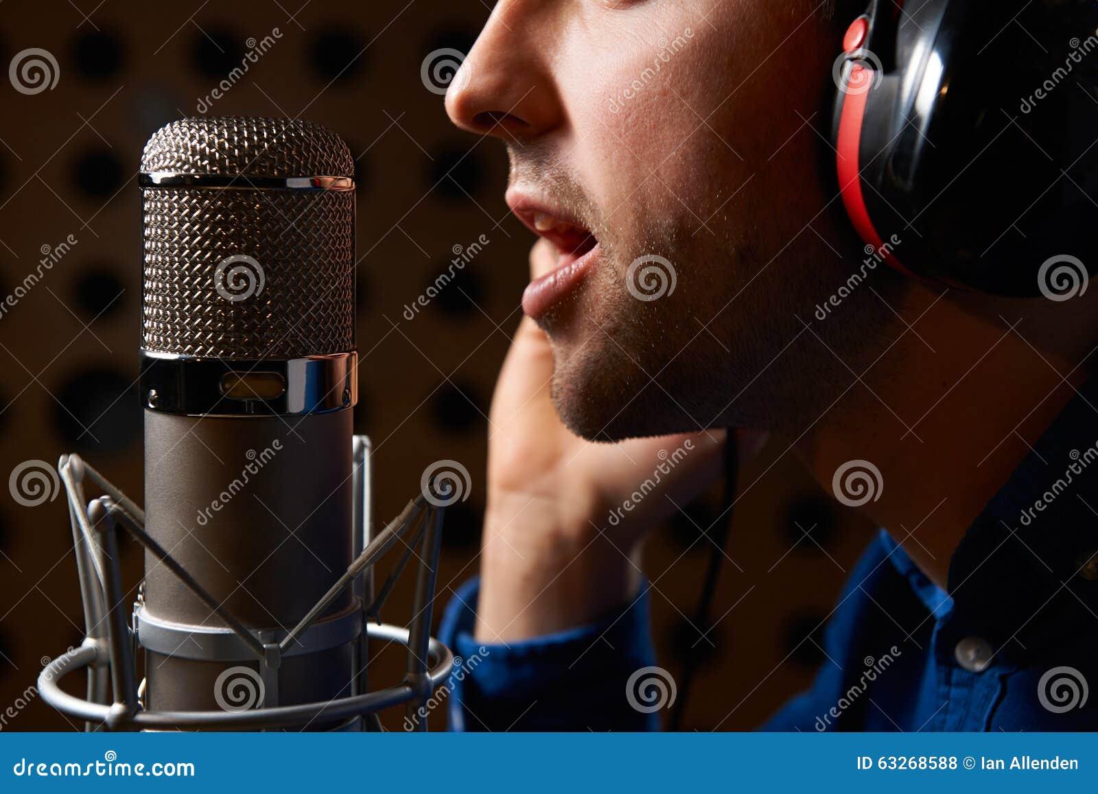 唱歌入话筒的男性歌唱者在录音室
