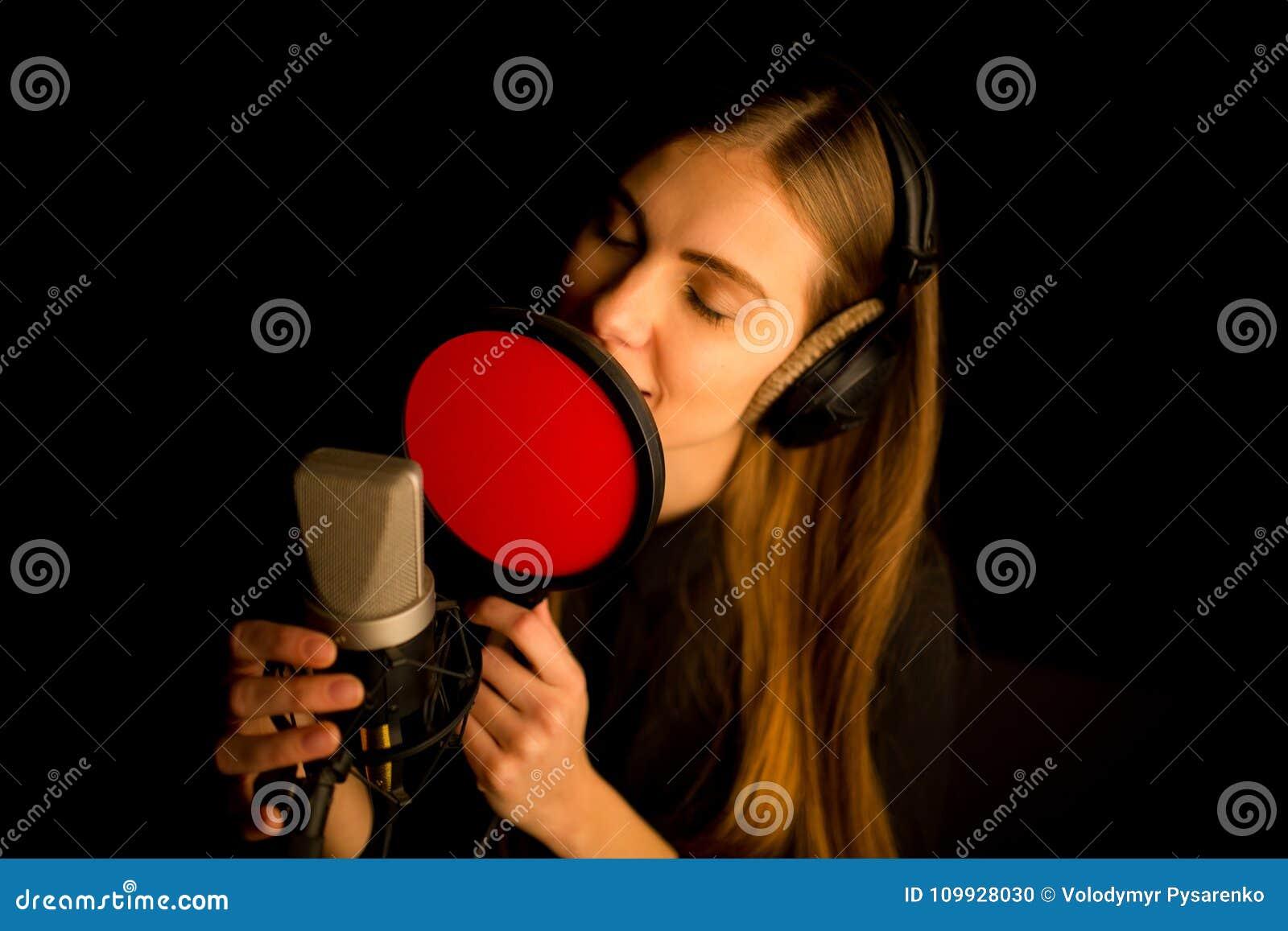 唱歌对话筒的女孩在演播室 创造新的歌曲的过程