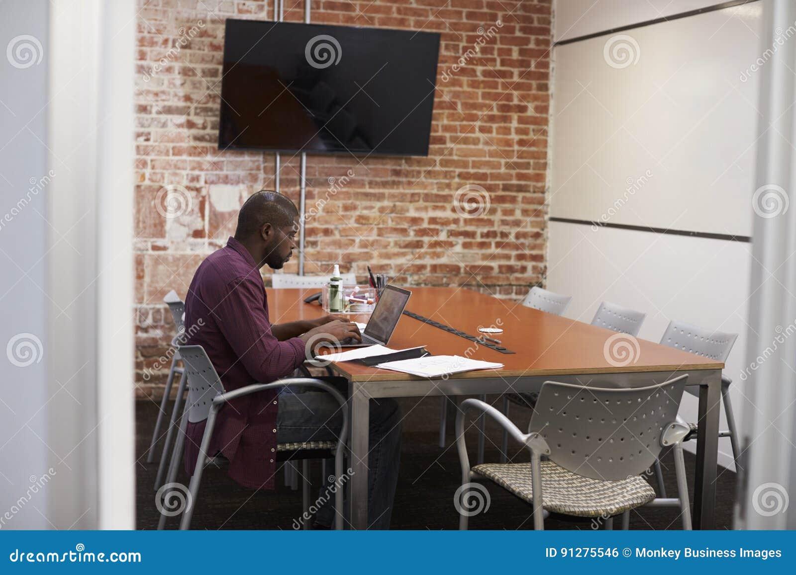 商人在研究膝上型计算机的会议室
