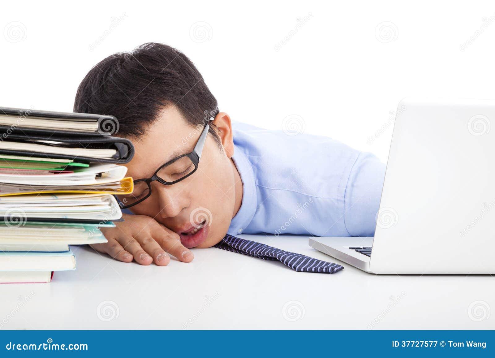 年轻商人太疲倦对睡着在书桌上