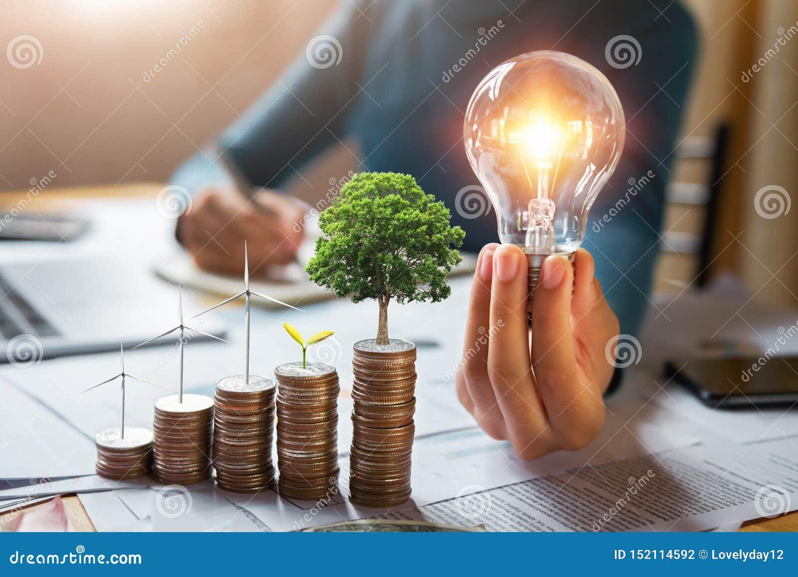 商人有涡轮的藏品电灯泡和树在硬币增长 概念保存的能量和财务会计